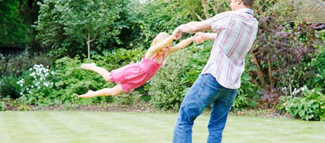 man spinning daughter in backyard
