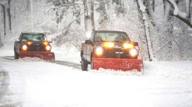 2 trucks plowing the road